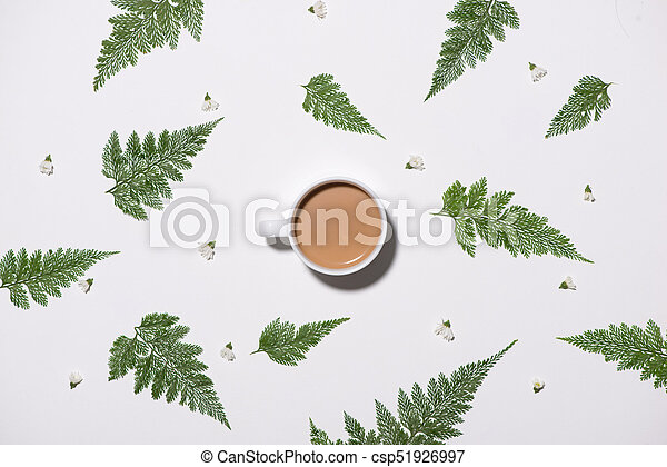 Flat lay of green leaves pattern with cup of coffee on white background - csp51926997