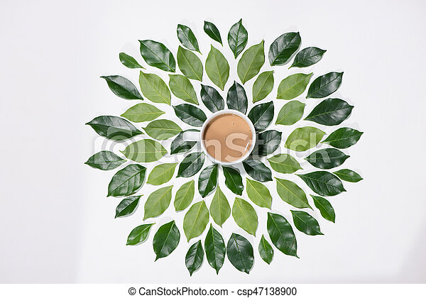 Flat lay of green leaves pattern with cup of coffee on white background - csp47138900