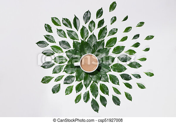 Flat lay of green leaves pattern with cup of coffee on white background - csp51927008