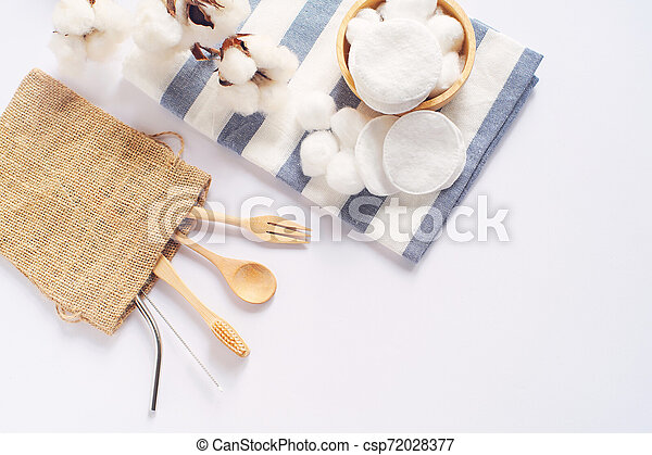 Flat lay of sustainable products, wooden spoon, stainless straw and natural cotton on white background and copy space, eco friendly and zero waste concept - csp72028377