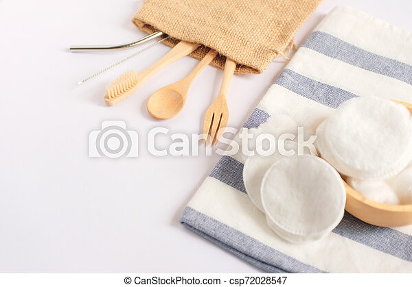 Flat lay of sustainable products, wooden spoon, stainless straw and natural cotton on white background and copy space, eco friendly and zero waste concept - csp72028547