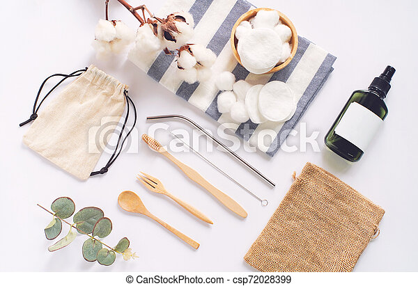 Flat lay of sustainable products, wooden spoon, stainless straw, organic cosmetic and natural cotton on white background, eco friendly and zero waste concept - csp72028399