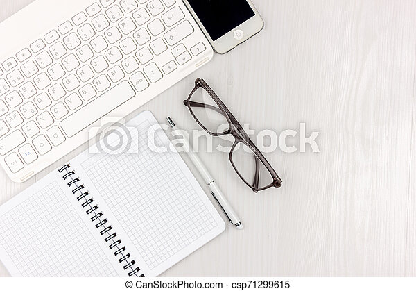 Flat lay photo of white office desk with laptop, smartphone, eyeglasses, notebook and pen with copy space background. Mockup - csp71299615