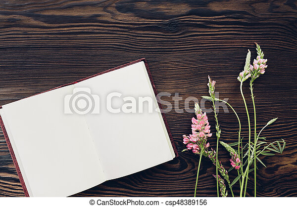 flat lay white flowers and a diary on a wooden background, top view. mock up