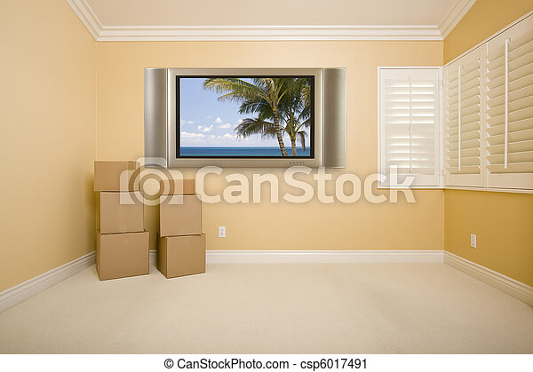 Flat panel television on wall in empty room with boxes. Flat panel ...