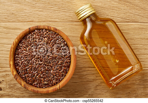 Flax Seeds In Bowl And Flaxseed Oil In Glass Bottle On Wooden Background Top View Close Up Selective Focus