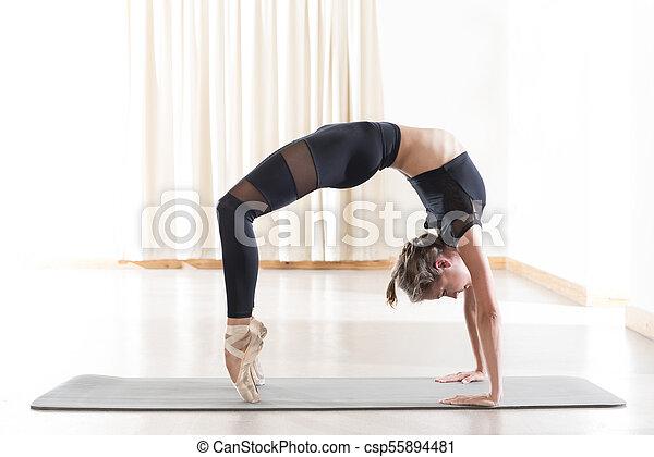 flexible young woman doing an advanced yoga crab pose