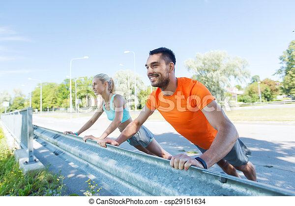 Una pareja feliz haciendo flexiones al aire libre - csp29151634