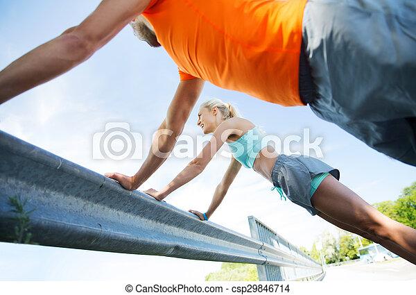 Una pareja feliz haciendo flexiones al aire libre - csp29846714