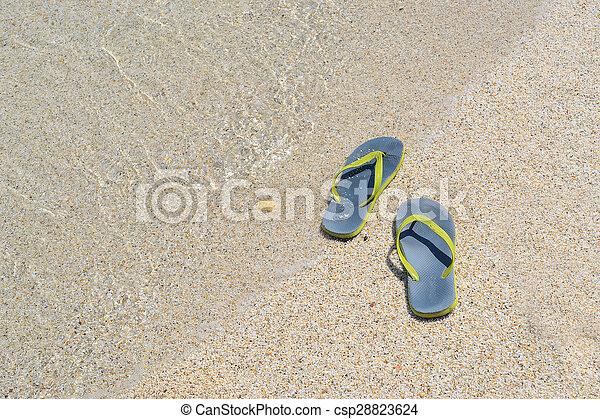 flip flops on a sandy beach  - csp28823624