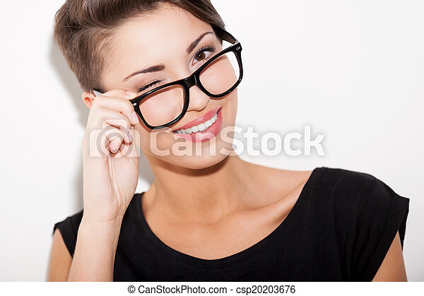 Flirty beauty. Portrait of beautiful young short hair woman adjusting her glasses and winking to you - csp20203676
