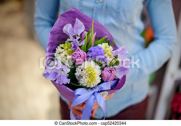 Florist holding a beautiful and cute purple bouquet of flowers - csp52420344