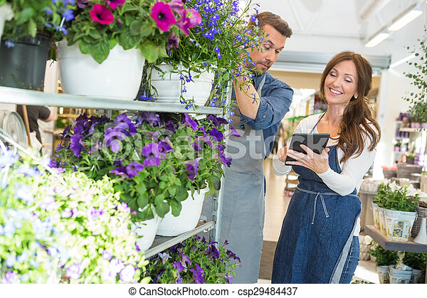 Florist Looking At Female Colleague Using Tablet Computer
