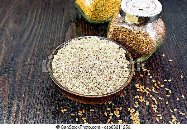 Flour linen in bowl with seeds in glass jars on dark board - csp63211259