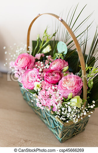 Flower arrangement in basket with ranunculus and small pink stock flower arrangement in basket with dark and light pink ranunculus and austeria view from above with central flowers in focus and other flowers blurred mightylinksfo