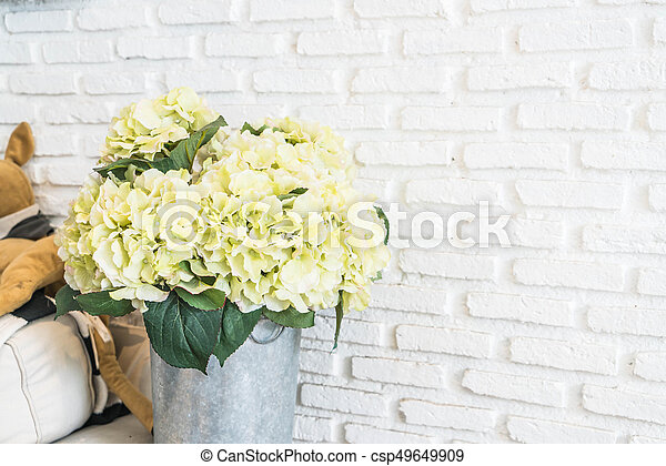 flower in pot with white brick wall background - csp49649909