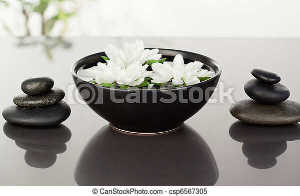 Flowers floating surrounded by stacks of black pebbles - csp6567305