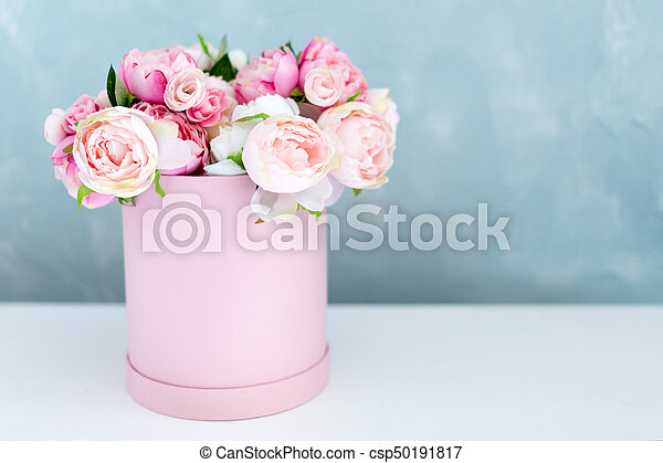 Flowers in round luxury present box. Bouquet of pink and white peonies in paper box. Mock-up of hat box of flowers with free copyspace for text. Interior decoration in in pastel colors