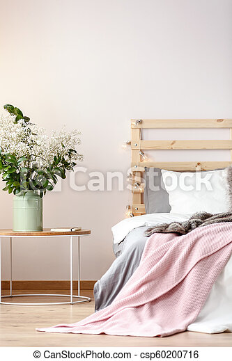 Flowers On Table Next To Bed With Pink Blanket And Wooden Headboard In Bedroom Interior Real Photo Canstock