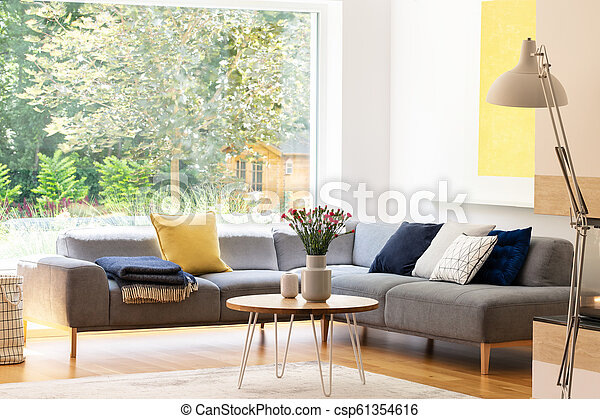 Astonishing Flowers On Table Next To Grey Corner Sofa With Cushions In Apartment Interior With Window Real Photo Uwap Interior Chair Design Uwaporg