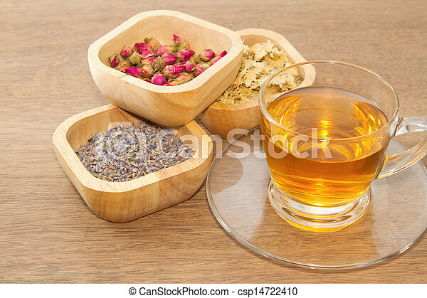 Flowers tea collection in a wooden bowl with cup of tea - csp14722410