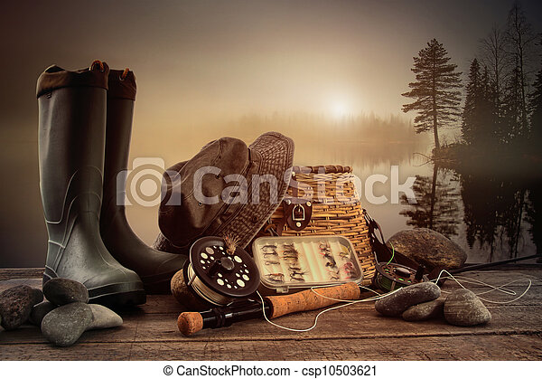 Fly fishing equipment on deck with view of a misty lake - csp10503621