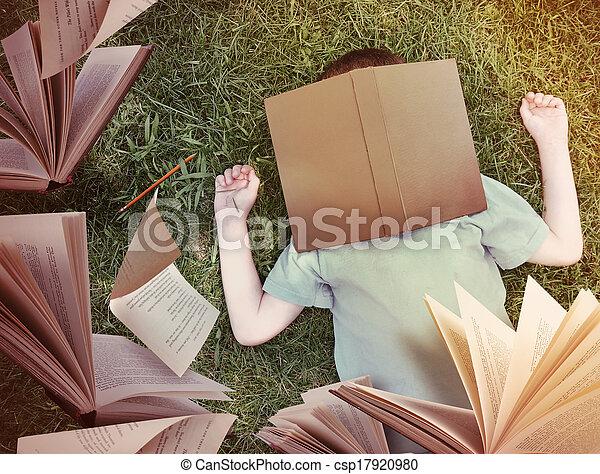 Flying Books Around Sleeping Boy in Grass - csp17920980