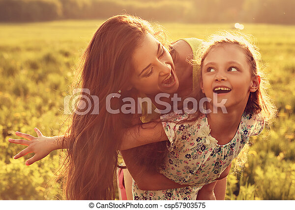 Flying kid girl laughing with happy enjoying mother on sunset bright summer background. Closeup toned color portrait. - csp57903575