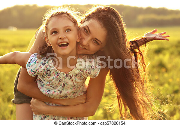 Flying kid girl laughing with happy enjoying mother on sunset bright summer background. Closeup portrait. - csp57826154
