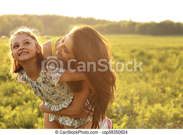 Flying kid girl laughing with happy enjoying mother on sunset bright summer background. Closeup portrait. - csp58350824