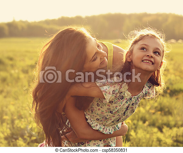 Flying kid girl laughing with happy enjoying mother on sunset bright summer background. Closeup toned portrait. - csp58350831