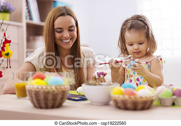 Focus little girl painting easter eggs with her mother  - csp19222560