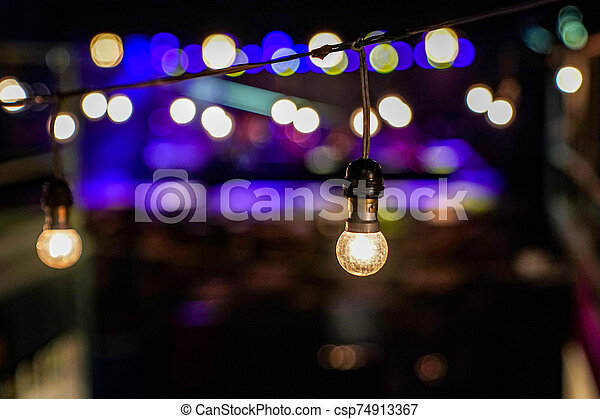 Focus on Vintage circle hanging lamp on the line with blur outdoor concert in the night bokeh background. - csp74913367