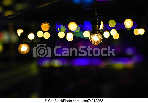 Focus on Vintage circle hanging lamp on the line with blur outdoor concert in the night bokeh background. - csp74913368
