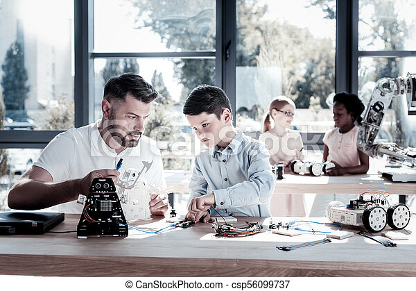 Focused youngster working on robot with his teacher - csp56099737