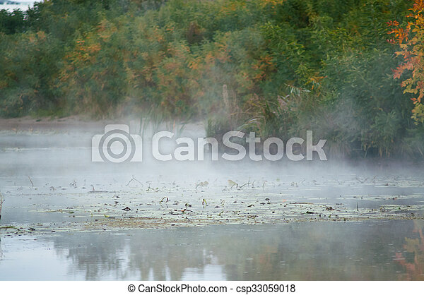 fog on an autumn river with green forest - csp33059018