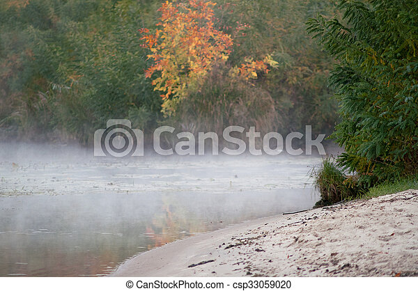 fog on an autumn river with green forest - csp33059020