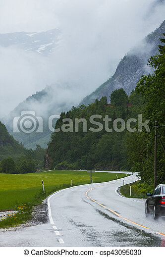 Foggy landscape with road in norwegian mountains - csp43095030