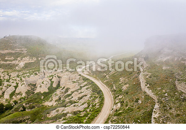 foggy morning over a windy road - csp72250844