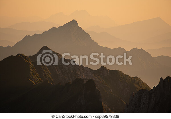 Foggy sunset with beautiful silhouette of mountain range in Switzerland - csp89579339
