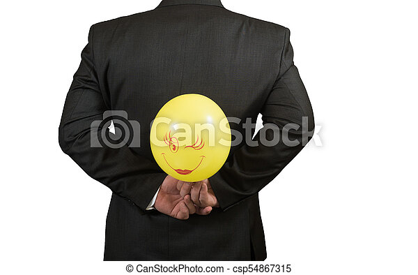 Fool's day is businessman with a balloon behind his back, isolated - csp54867315
