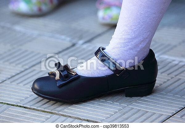 Foot schoolgirl in black shoes and