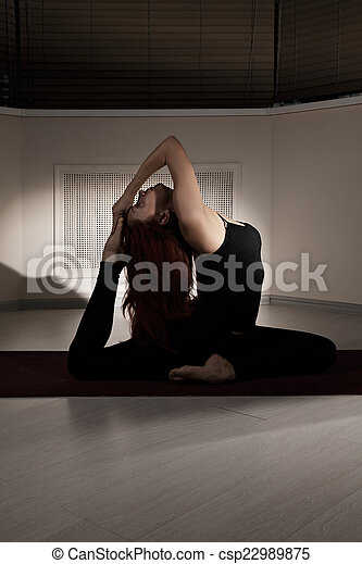 foot to head yoga pose in a dark gym