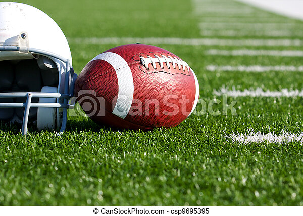 Football and Helmet on the Field - csp9695395