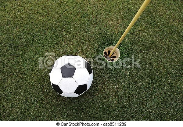 Football big ball at golf field hole - csp8511289