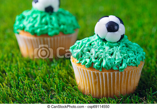 Football party, birthday decorated cupcake on green grass background. Close up. - csp69114550