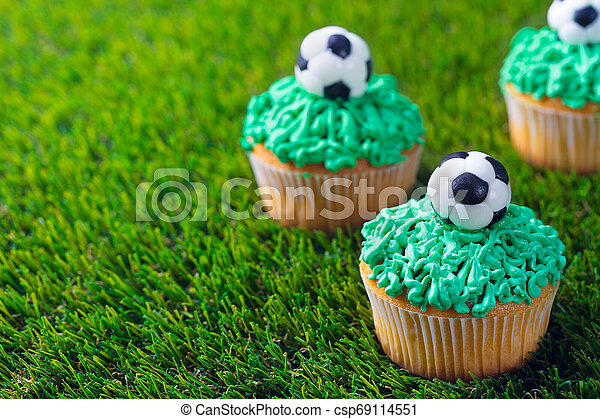 Football party, birthday decorated cupcake on green grass background. Copy space. - csp69114551