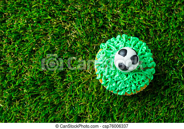 Football party, birthday decorated cupcake on green grass background. Copy space. Top view. - csp76006337