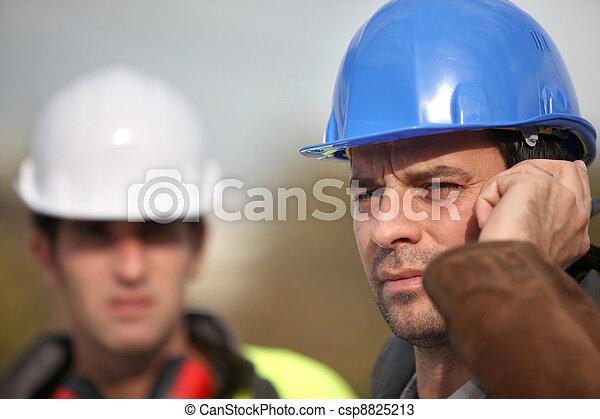 Foreman communicating via radio - csp8825213
