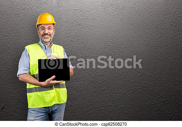 foreman smiling and showing a tablet - csp62508270